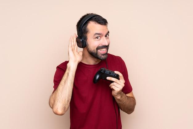 Человек играет с контроллером видеоигры над изолированной стеной, слушая что-то, положив руку на ухо