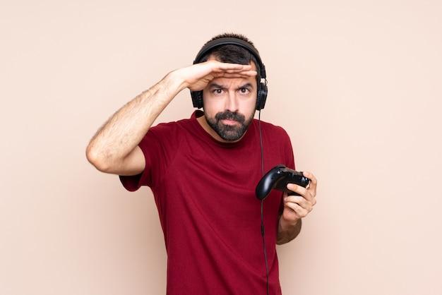 何かを見て手で遠くを見ている孤立した壁を越えてビデオゲームコントローラーで遊ぶ男
