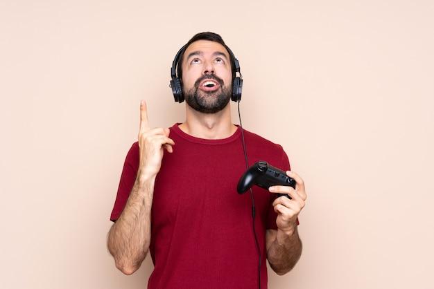 上向きと驚いた分離壁を越えてビデオゲームコントローラーで遊ぶ男