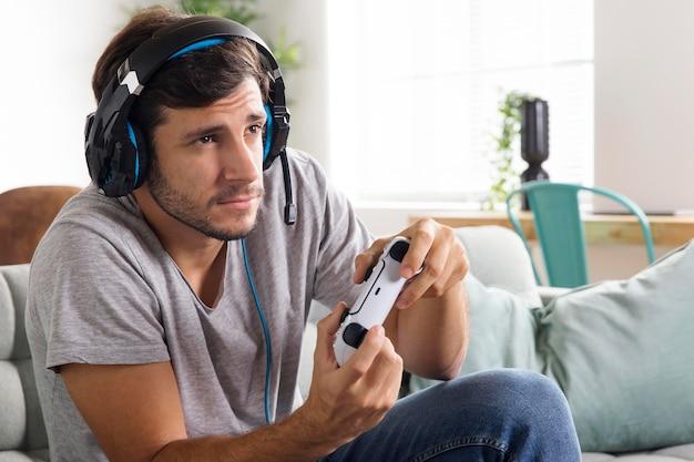 ソファでコントローラーで遊ぶ男