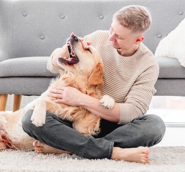 골든 리트리버 강아지와 놀고 그를 바닥에 앉아 쓰다듬는 남자