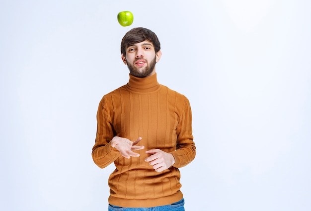 Man playing with a green apple and throwing it up.