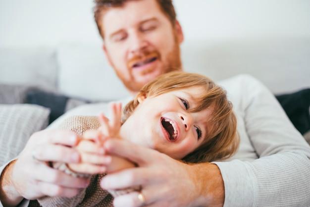 笑っている息子のソファの上で遊ぶ男