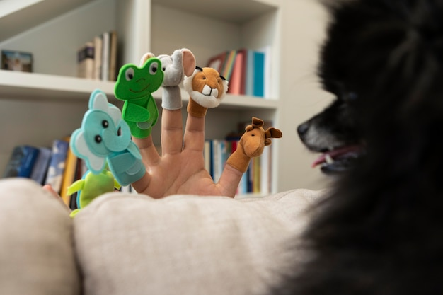 Man playing with puppets next to his dog
