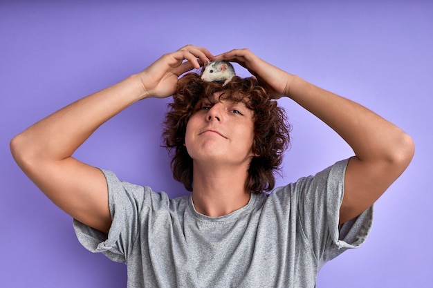 Man playing with rat domestic animal, he doesn't afraid of domestic mouse, isolated on purple studio wall, having fun spending time with pet at home