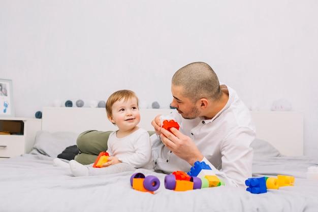 Человек играет с улыбкой маленького ребенка с игрушкой строительных блоков