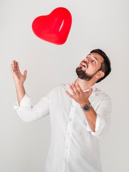 Man playing with valentines balloon