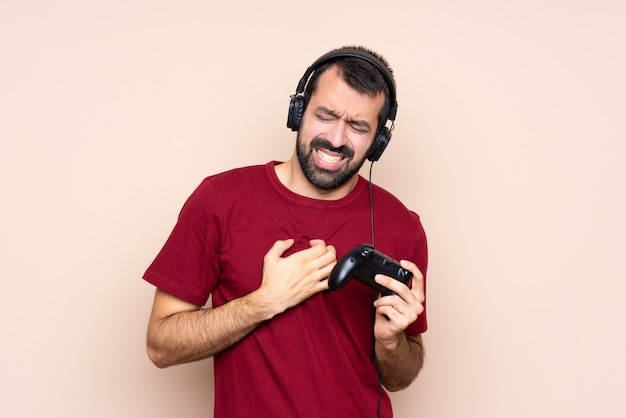 Man playing with a video game controller having a pain in the heart