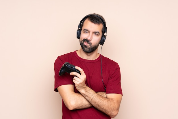 Man playing with a video game controller over isolated wall feeling upset