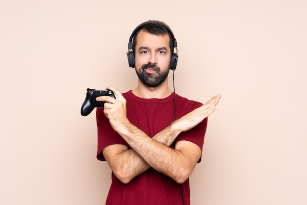 Man playing with a video game controller over isolated wall making no gesture