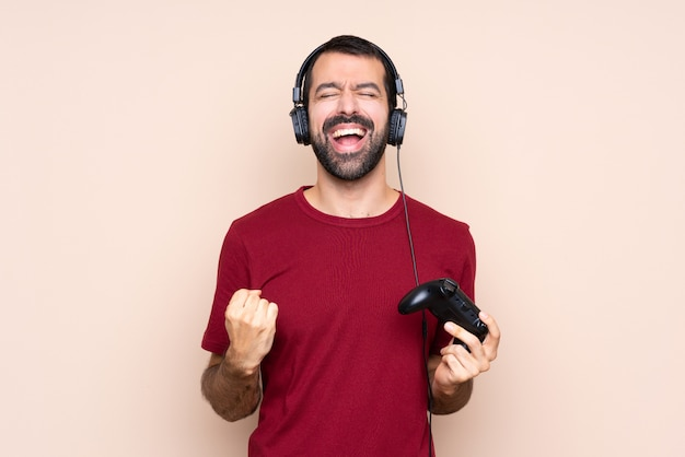 Man playing with a video game controller over isolated wall shouting to the front with mouth wide open