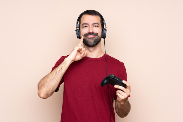 Man playing with a video game controller over isolated wall smiling with a happy and pleasant expression