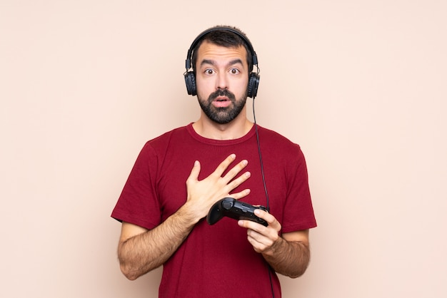 Man playing with a video game controller over isolated wall surprised and shocked while looking right
