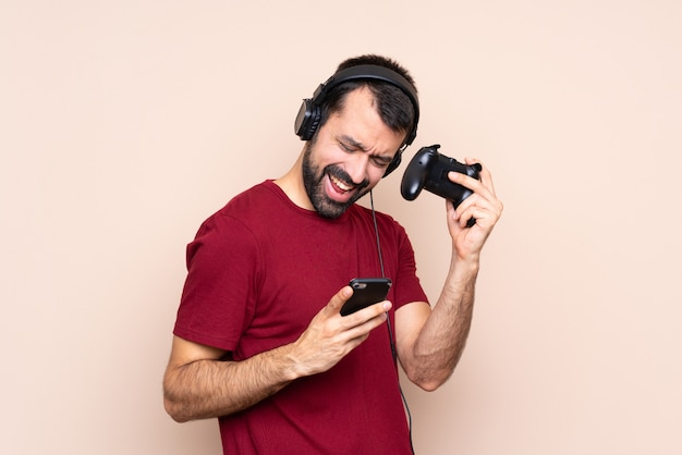 Man playing with a video game controller over isolated wall with phone in victory position