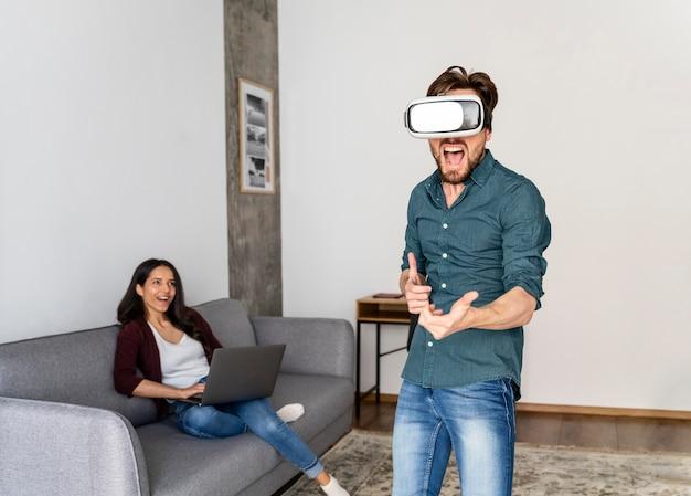 Uomo che gioca con le cuffie da realtà virtuale a casa