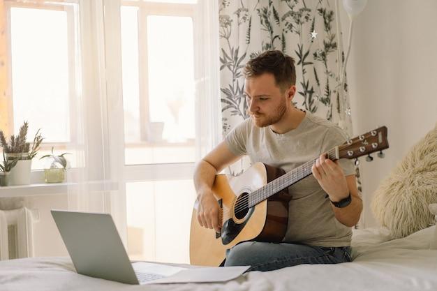 남자는 온라인 수업에서 어쿠스틱 기타를 연주