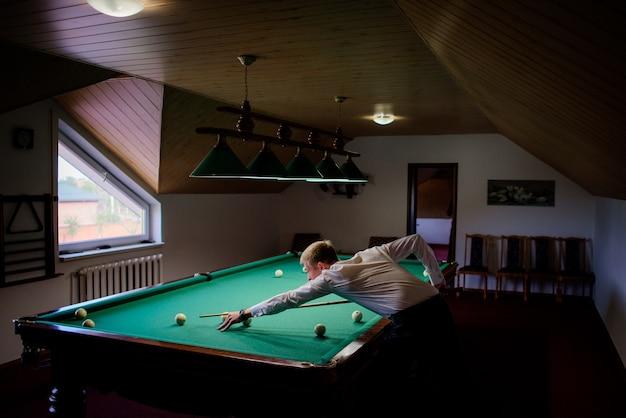 Man plays billiard in a dark room under the roof