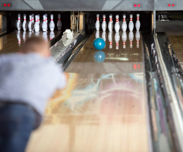 A man plays bowling throwing a ball in the pins.