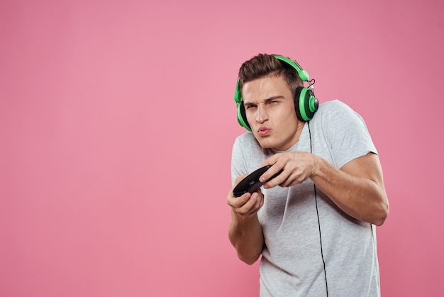 A man plays a computer game in consoles with joysticks in headphones with a laptop