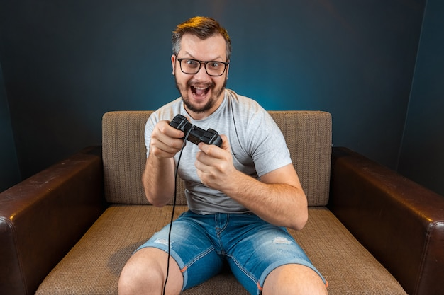 A man plays the console, video games react strongly and emotionally while sitting on the couch. day off, entertainment, leisure.