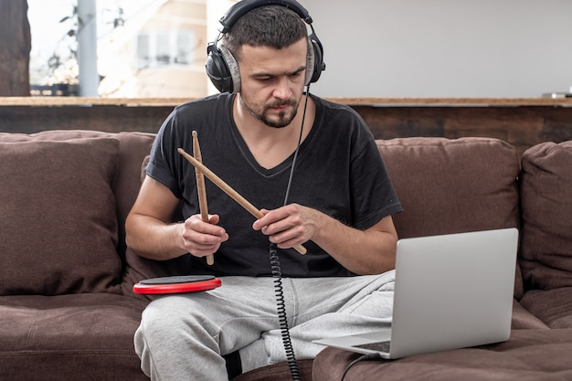 A man plays the drum and looks at the laptop screen. the concept of online music lessons, video conferencing lessons.