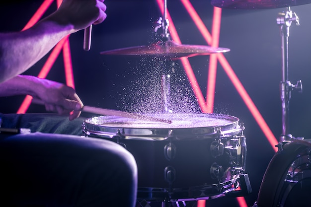 The man plays the drums, on the background of colored lights