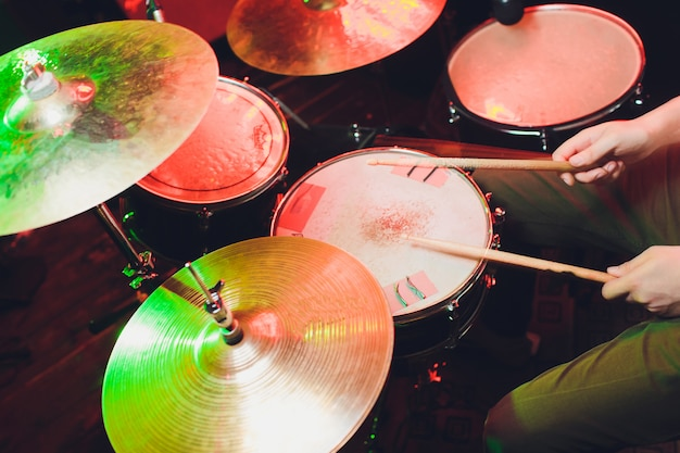 Man plays drums, game is on working drum with sticks close-up. on background of colored lights with splashes of water. musical concept with working drum.