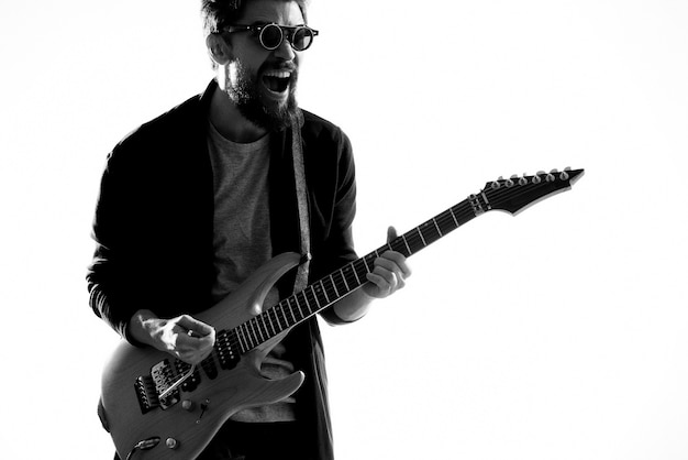 A man plays an electric guitar, black and white photo