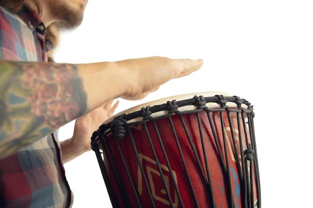 남자는 민족 드럼 darbuka 타악기를 연주하고 흰색 스튜디오 배경에 고립 된 음악가를 닫습니다. 젬베, 봉고를 리듬에 맞춰 두드리는 남성 손. 수제 악기, 세계 문화 소리.