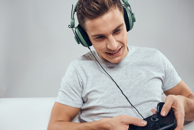 A man plays a game in consoles with controller and headphones