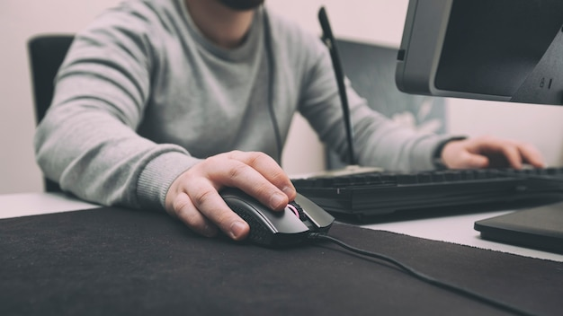 A man plays games on the computer in the office at the time when he has to work
