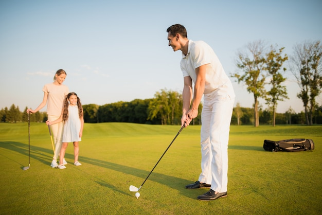 Man plays golf with wife and kid sport hobby.