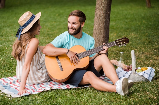 Man plays guitar for his girlfriend on the picnic in the park in the summer on sunset
