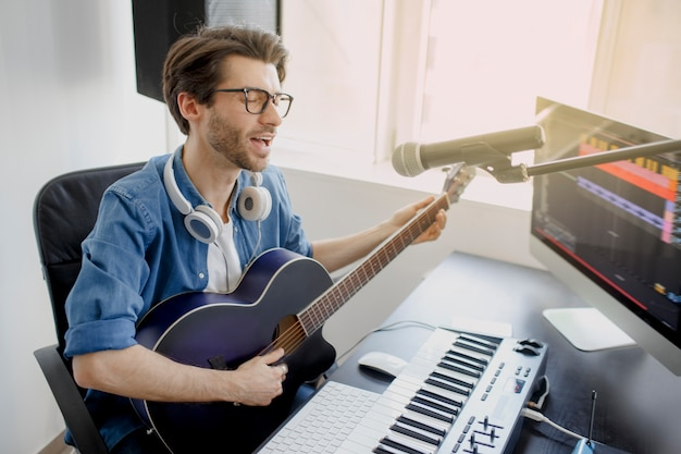 Man plays guitar and singing and produce electronic soundtrack or track in project at home. male music arranger composing song on midi piano and audio equipment in digital recording studio.