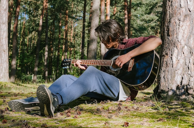 A man plays the guitar while sitting in the forest near a tree. against the backdrop of nature.