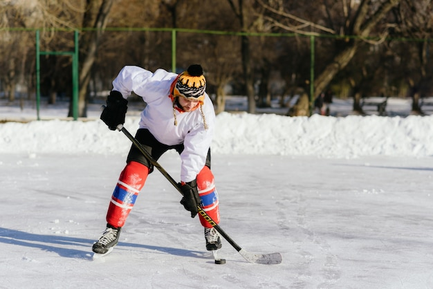 The man plays hockey on the rink