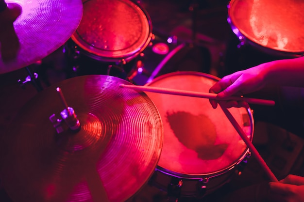 Man plays musical percussion instrument with sticks closeup on black