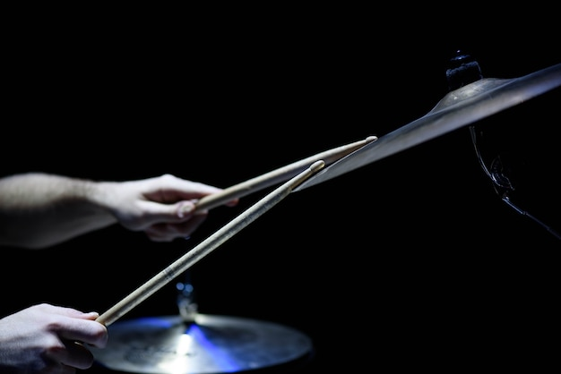 남자는 검은 배경에 스틱 근접 촬영, 작업 드럼과 음악 개념, 무대에서 아름다운 조명으로 뮤지컬 타악기를 연주