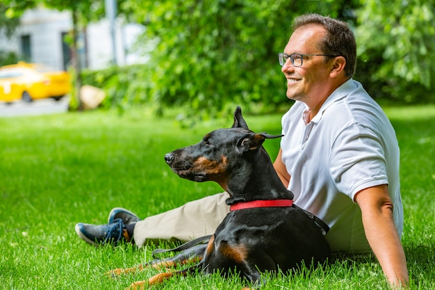 Man plays in the park with dobermann