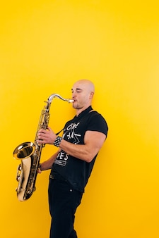 Man plays the saxophone  on a yellow wall