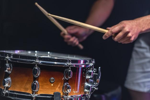 Un uomo suona un rullante con dei bastoncini, un batterista suona uno strumento a percussione, primo piano.