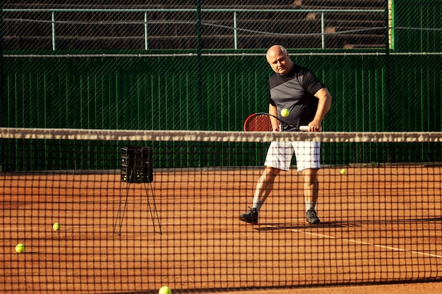 Man plays tennis on the court. active lifestyle and health.