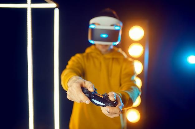 남자는 빛나는 큐브, 정면도에서 가상 현실 헬멧과 게임 패드를 사용하여 게임을합니다. 다크 플레이 클럽 인테리어, 3d 비전을 갖춘 vr 기술