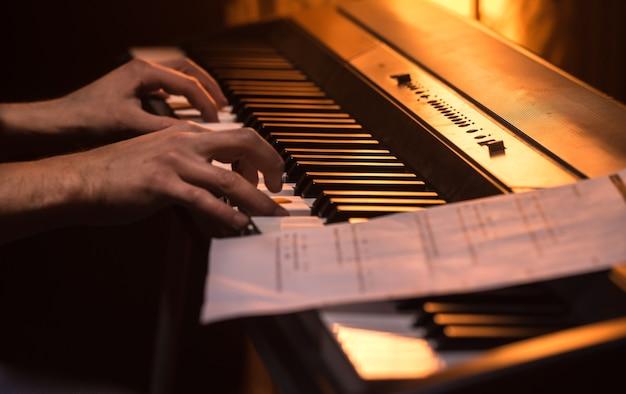 男はピアノ、クローズアップ、美しい色の背景、音楽活動の概念でノートを演奏します