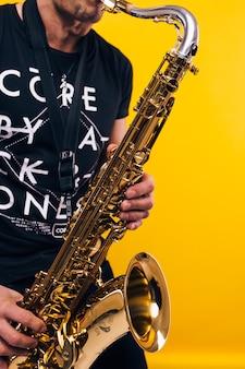 Мужчина играет на саксофоне на желтой стене
