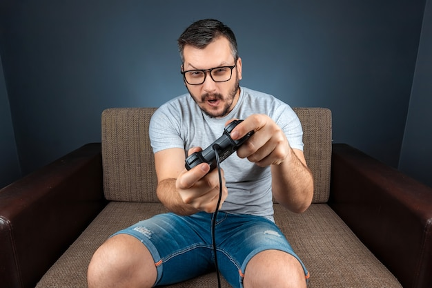 A man plays a video game console while sitting on a sofa. day off, entertainment, leisure.