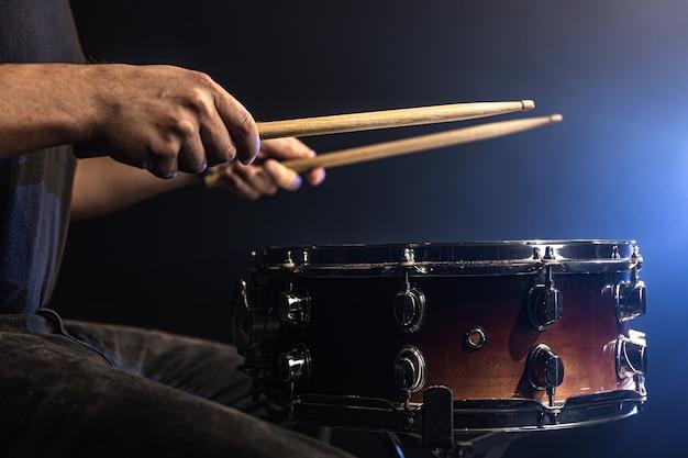 Un uomo gioca con i bastoni su un tamburo, un batterista suona uno strumento a percussione, primo piano.