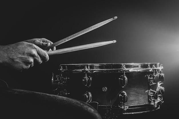 Un uomo gioca con i bastoncini su un tamburo, un batterista suona uno strumento a percussione, copia spazio, monocromatico.