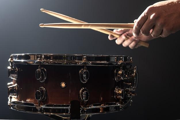 Un uomo gioca con i bastoncini su un tamburo, un batterista suona uno strumento a percussione, copia spazio.