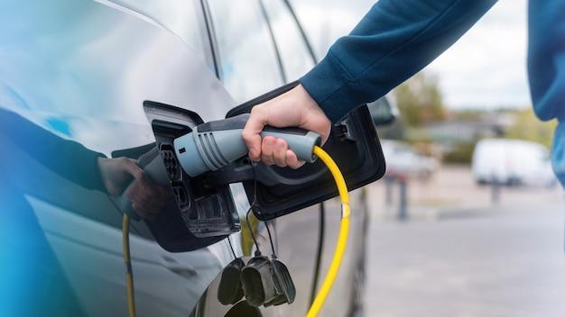 Uomo che collega il caricabatterie a un'auto elettrica alla stazione di ricarica